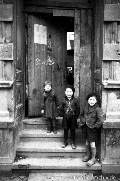 Drei Kinder vor einer provisorischen Haustür in Köln