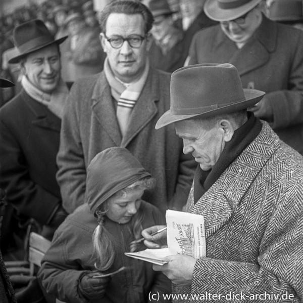 Sepp Herberger gibt ein Autogramm.